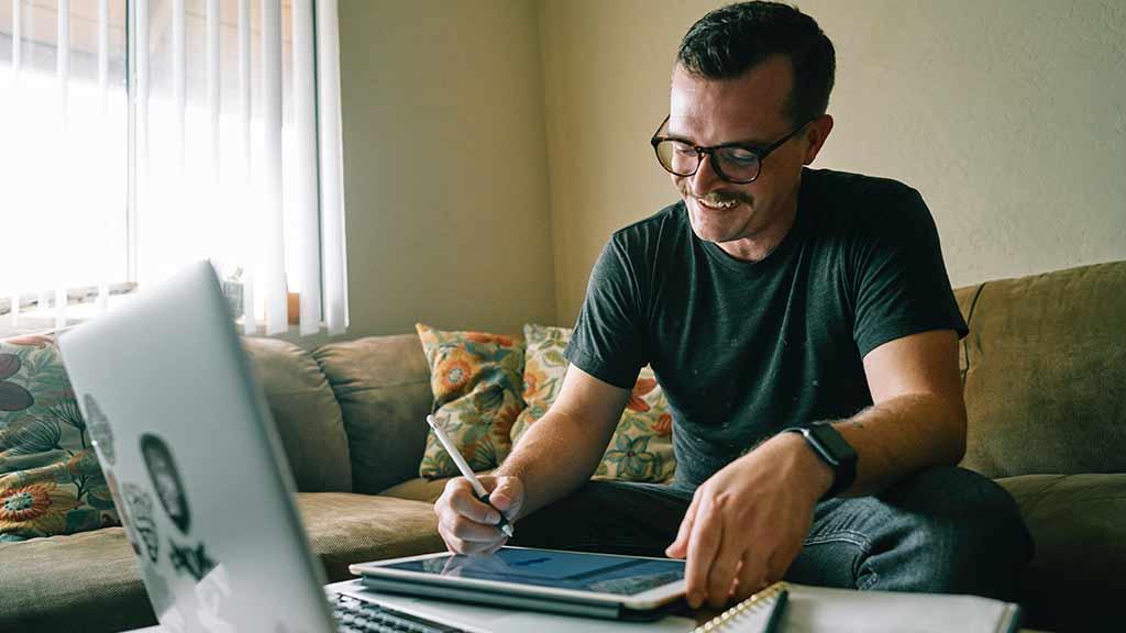 Mann Homeoffice Spaß rille Arbeit sitzen Couch Laptop Tablet lachen