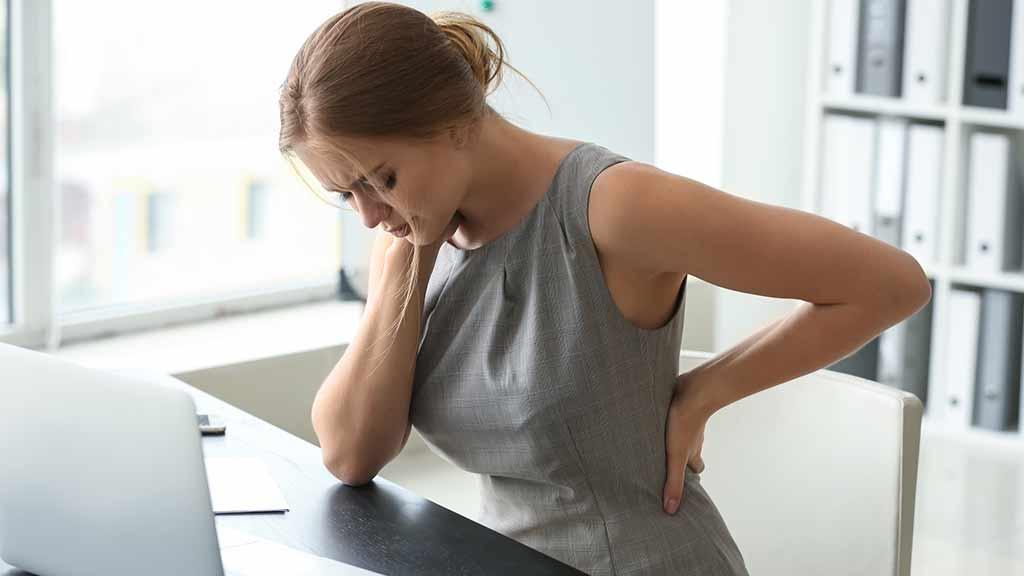 Homeoffice Arbeit Frau Rücken Schmerzen sitzen Belastungen Gefährdungsbeurteilung