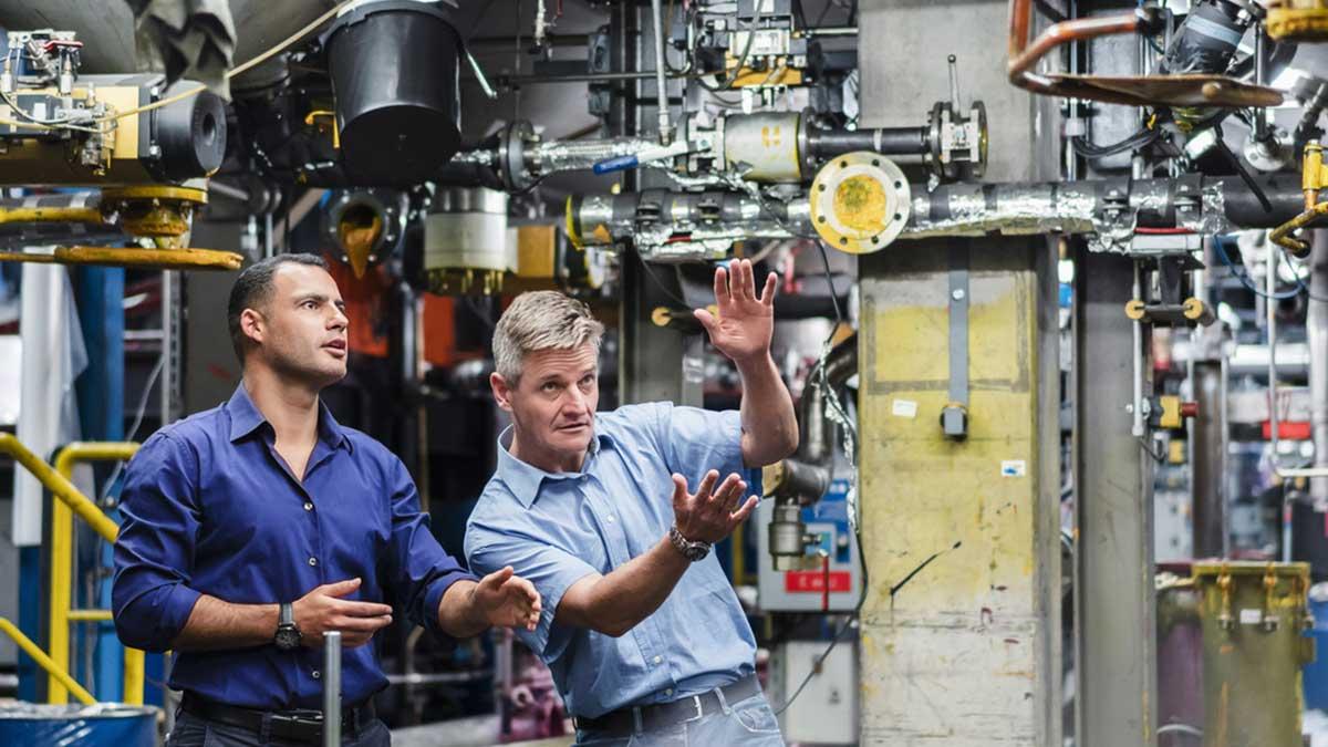 Zwei Fachkräfte für Arbeitssicherheit beim Gespräch in einer großen Industriehalle